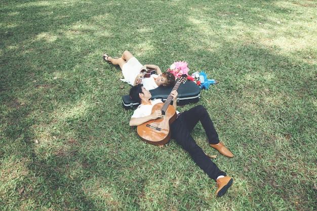 Paar in liefde met gitaarspelen in de natuur