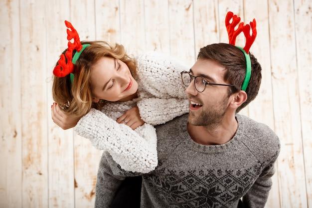Paar in nep herten hoorns poseren hebben plezier over houten muur