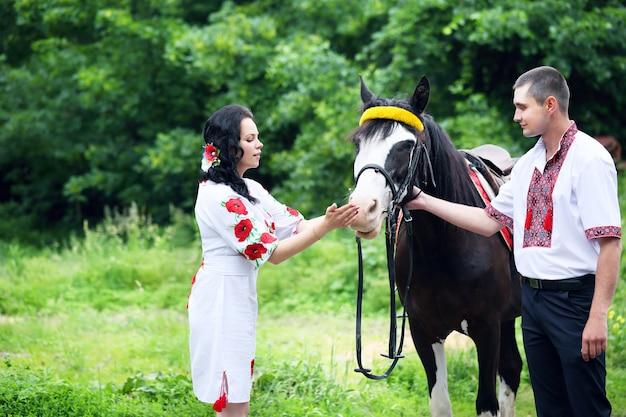 Paar in oekraïense kostuums met een paard