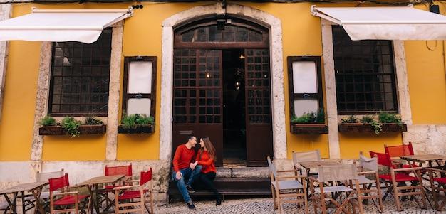 Paar in rode truien zittend op trappen bij café ingang. veel tafels en stoelen voor het café. mooi pand met grote deur.