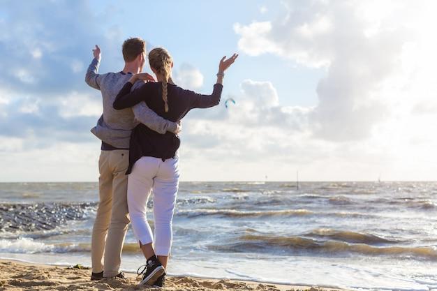 Paar in romantische zonsondergang op oceaanstrand