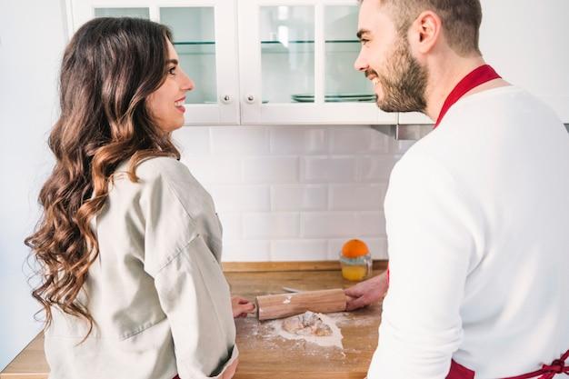 Paar in schorten die deeg koken