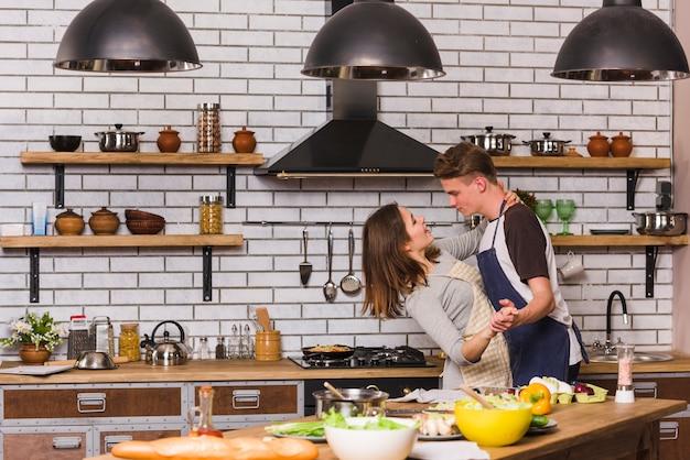 Paar in schorten die in keuken dansen