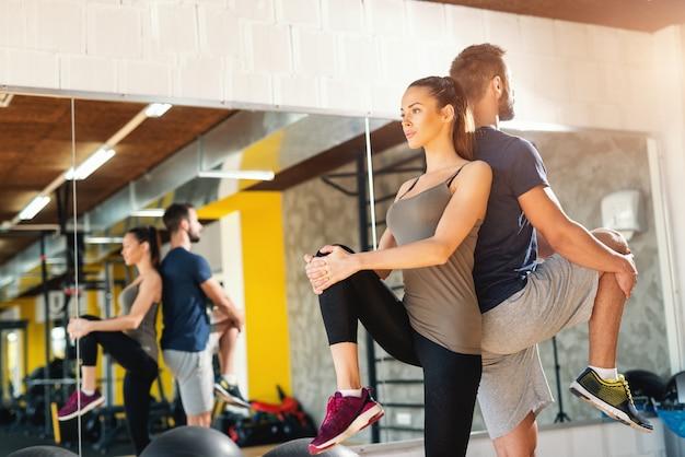 Paar in sportschool leunend op elkaar rug en uitrekkende benen. gym interieur, hun weerspiegeling in spiegel.