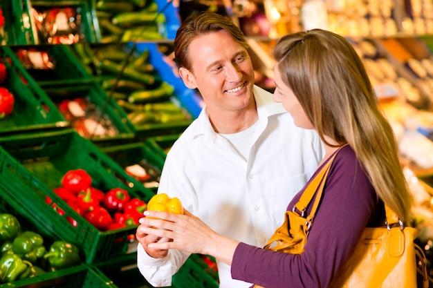 Paar in supermarkt boodschappen doen