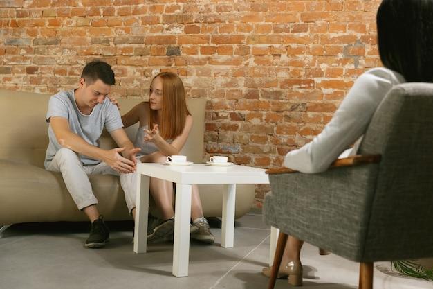 Paar in therapie of huwelijkstherapie. psycholoog, vertrouwenspersoon, therapeut of relatieadviseur die advies geeft. man en vrouw zittend op een sessie psychotherapie. familie, geestelijke gezondheidsconcept.