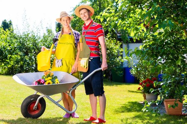 Paar in tuin met gieter en kruiwagen