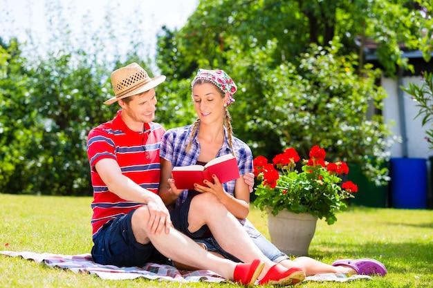 Paar in tuin op deken leesboek