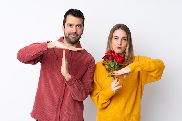 Paar in valentijnsdag bedrijf bloemen over geïsoleerde muur maken stop gebaar met haar hand om een handeling te stoppen