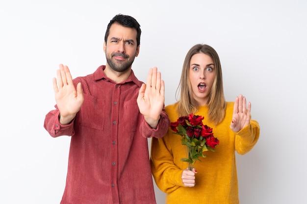 Paar in valentijnsdag bedrijf bloemen over geïsoleerde muur maken stop gebaar voor teleurgesteld met een mening