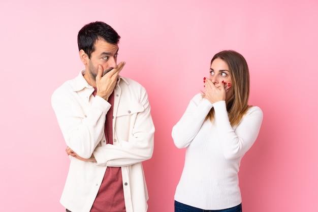 Paar in valentijnsdag over geïsoleerde roze muur die mond behandelen met handen voor ongepast te zeggen iets