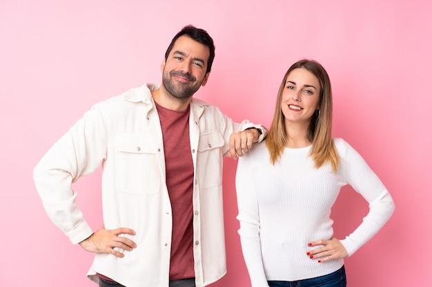 Paar in valentijnsdag over geïsoleerde roze muur poseren met armen op heup en glimlachen