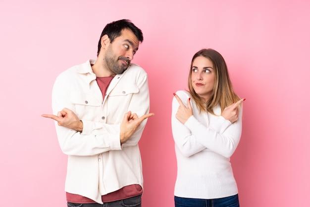 Paar in valentijnsdag over geïsoleerde roze muur wijzend op de zijtakken met twijfels