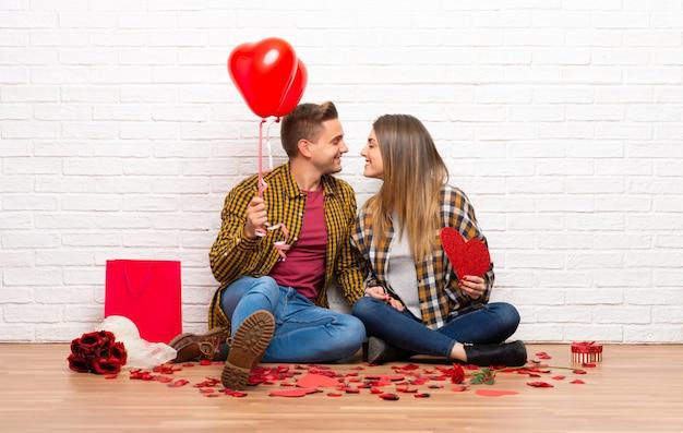 Paar in valentijnskaartdag bij binnen het houden van een hartsymbool en ballons