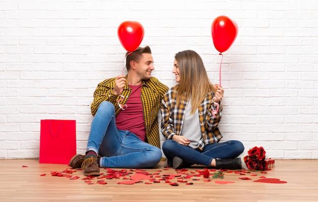Paar in valentijnskaartdag bij binnen met ballons met hartvorm