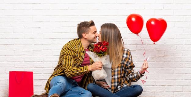 Paar in valentijnskaartdag bij binnen met bloemen en ballons met hartvorm