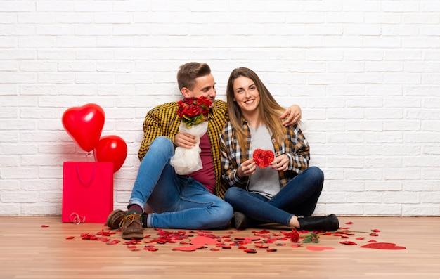 Paar in valentijnskaartdag bij binnen met bloemen en giften