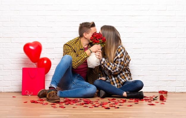 Paar in valentijnskaartdag bij binnen met bloemen en het kussen