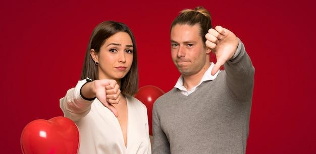 Paar in valentijnskaartdag die duim onderaan teken met negatieve uitdrukking toont