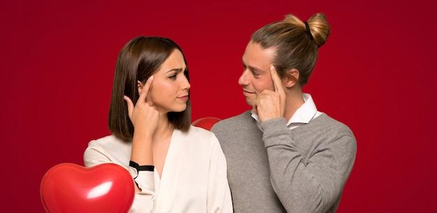 Paar in valentijnskaartdag die twijfels hebben en over rode achtergrond denken