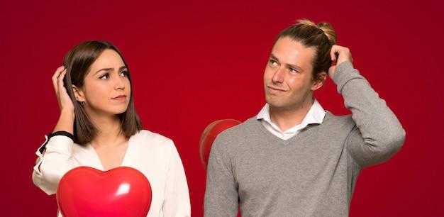 Paar in valentijnskaartdag die twijfels hebben terwijl het krassen van hoofd over rode achtergrond