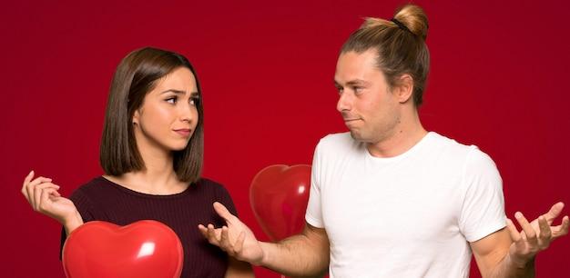 Paar in valentijnskaartdag die twijfels over rode achtergrond hebben