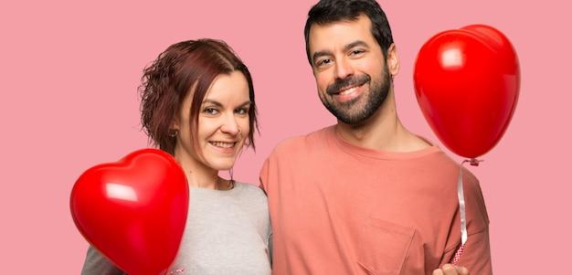 Paar in valentijnskaartdag met ballons met hartvorm over geïsoleerde roze achtergrond