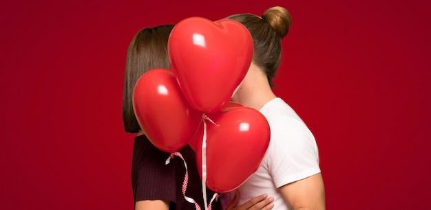 Paar in valentijnskaartdag met ballons met hartvorm over rode achtergrond