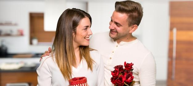 Paar in valentijnskaartdag met bloemen en giften in een huis