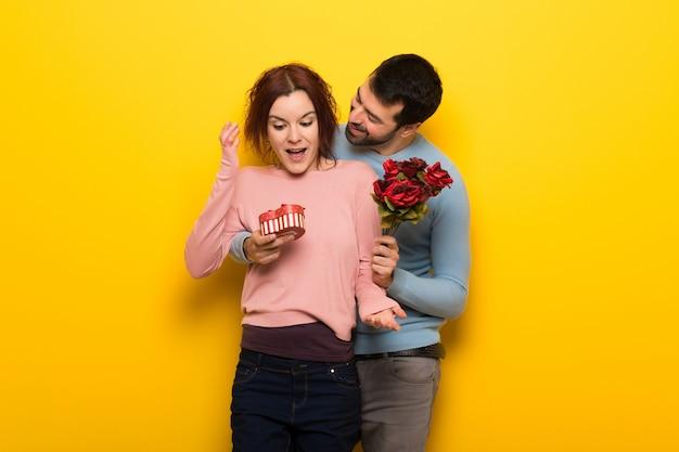 Paar in valentijnskaartdag met bloemen en giften
