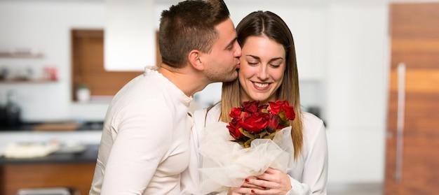 Paar in valentijnskaartdag met bloemen in een huis