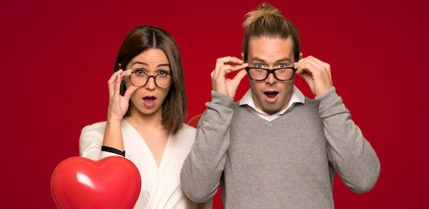Paar in valentijnskaartdag met glazen en verrast over rode achtergrond