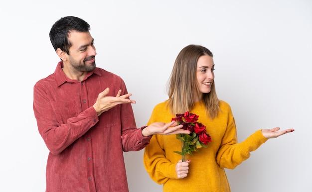 Paar in valentine day die bloemen over geïsoleerde muur houden die handen uitbreiden aan de kant voor het uitnodigen om te komen