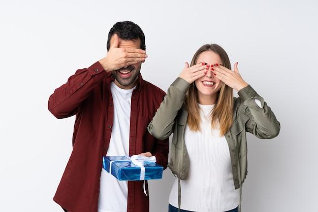 Paar in valentine day die een gift over geïsoleerde muur behandelen die ogen behandelen door handen