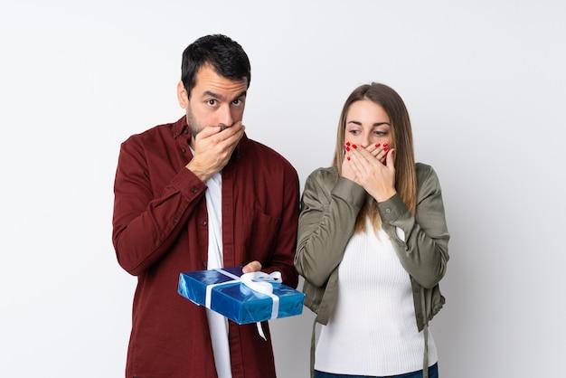 Paar in valentine day die een gift over geïsoleerde muur die mond behandelen met handen