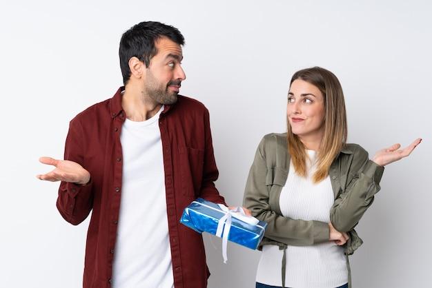 Paar in valentine day die een gift over geïsoleerde muur houden die twijfels hebben