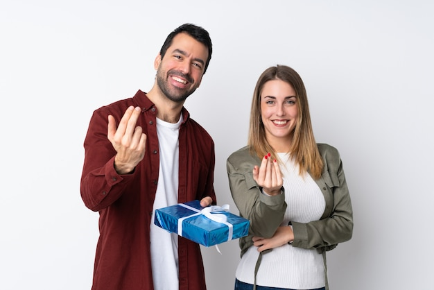 Paar in valentine day die een gift over geïsoleerde muur houden uitnodigend om met hand te komen