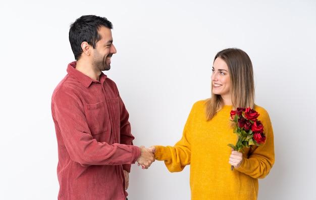 Paar in valentine day-holdingsbloemen over geïsoleerd muurhandenschudden na goede deal