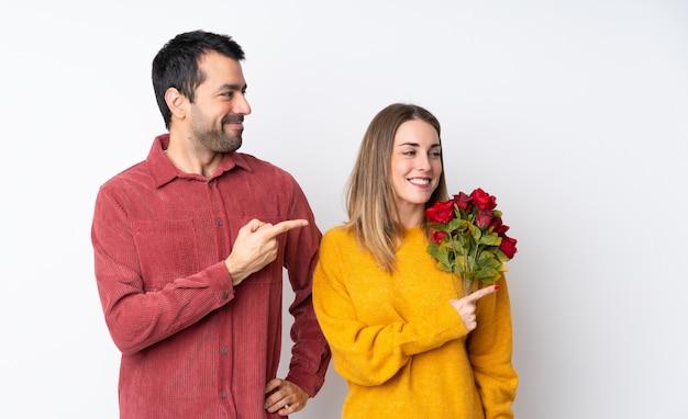 Paar in valentine day-holdingsbloemen over geïsoleerde muur die aan de kant richten om een product te presenteren