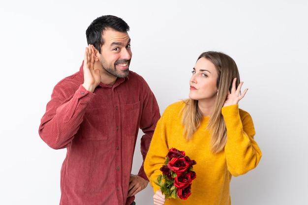 Paar in valentine day-holdingsbloemen over geïsoleerde muur die aan iets luisteren door hand op het oor te zetten