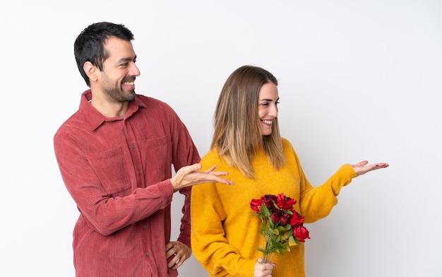 Paar in valentine day-holdingsbloemen over geïsoleerde muur die een idee voorstellen terwijl het kijken glimlachen naar