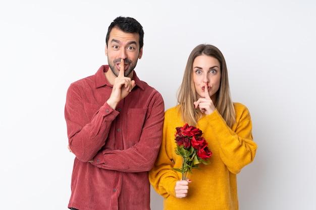 Paar in valentine day-holdingsbloemen over geïsoleerde muur die een teken van stiltegebaar tonen die vinger in mond zetten