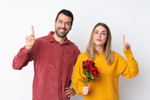Paar in valentine day-holdingsbloemen over geïsoleerde muur die en een vinger in teken van het beste tonen opheffen
