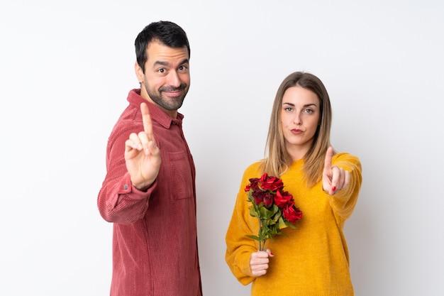 Paar in valentine day-holdingsbloemen over geïsoleerde muur die en een vinger tonen opheffen