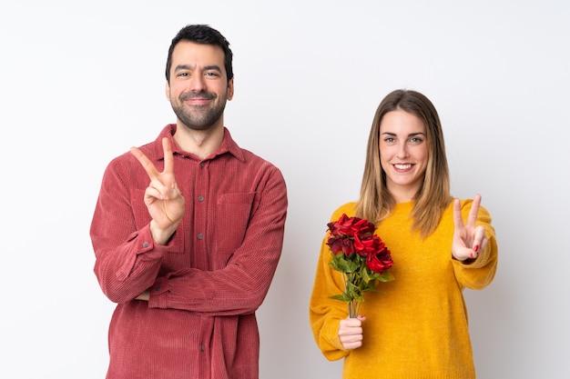 Paar in valentine day-holdingsbloemen over geïsoleerde muur die en overwinningsteken glimlachen tonen