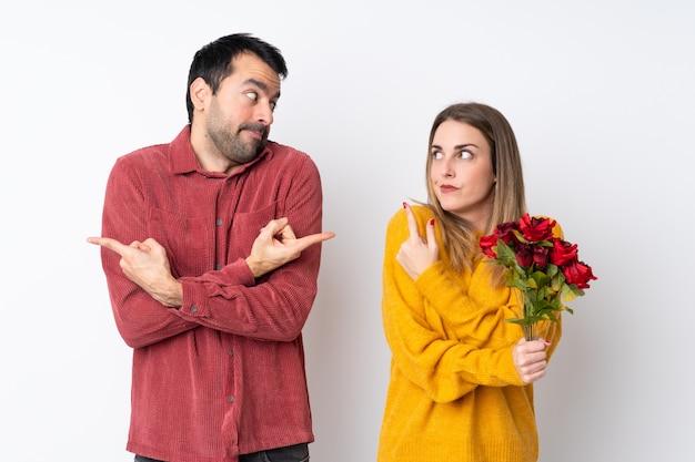 Paar in valentine day-holdingsbloemen over geïsoleerde muur die naar de zijkanten richten die twijfels hebben