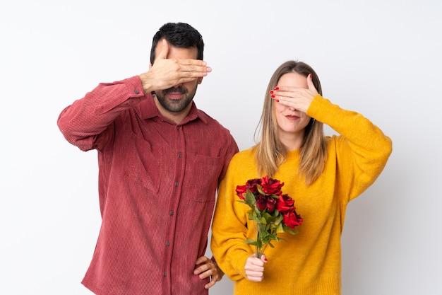 Paar in valentine day-holdingsbloemen over geïsoleerde muur die ogen behandelen door handen. wil niet iets zien