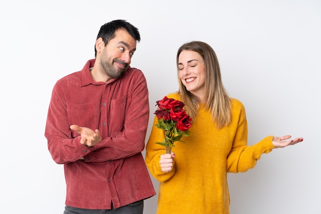 Paar in valentine day-holdingsbloemen over geïsoleerde muur die onbelangrijk gebaar maken terwijl het opheffen van de schouders