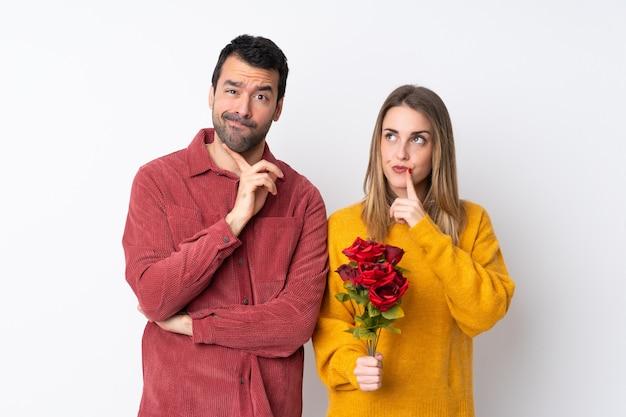 Paar in valentine day-holdingsbloemen over geïsoleerde muur die twijfels hebben terwijl omhoog het kijken