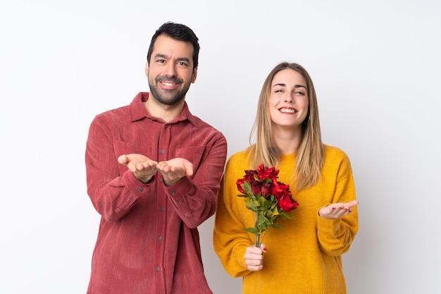 Paar in valentine day-holdingsbloemen over geïsoleerde muurholding copyspace denkbeeldig op de palm om een advertentie op te nemen